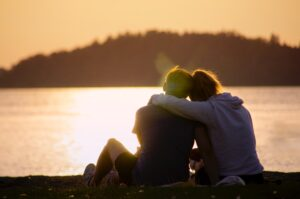 Two people sitting with arms around each others shoulders. They are sitting facing a lake with an island or tree covered land across the lake at sunset or sunrise.